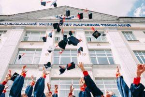 new graduates throwing their graduation hats upward